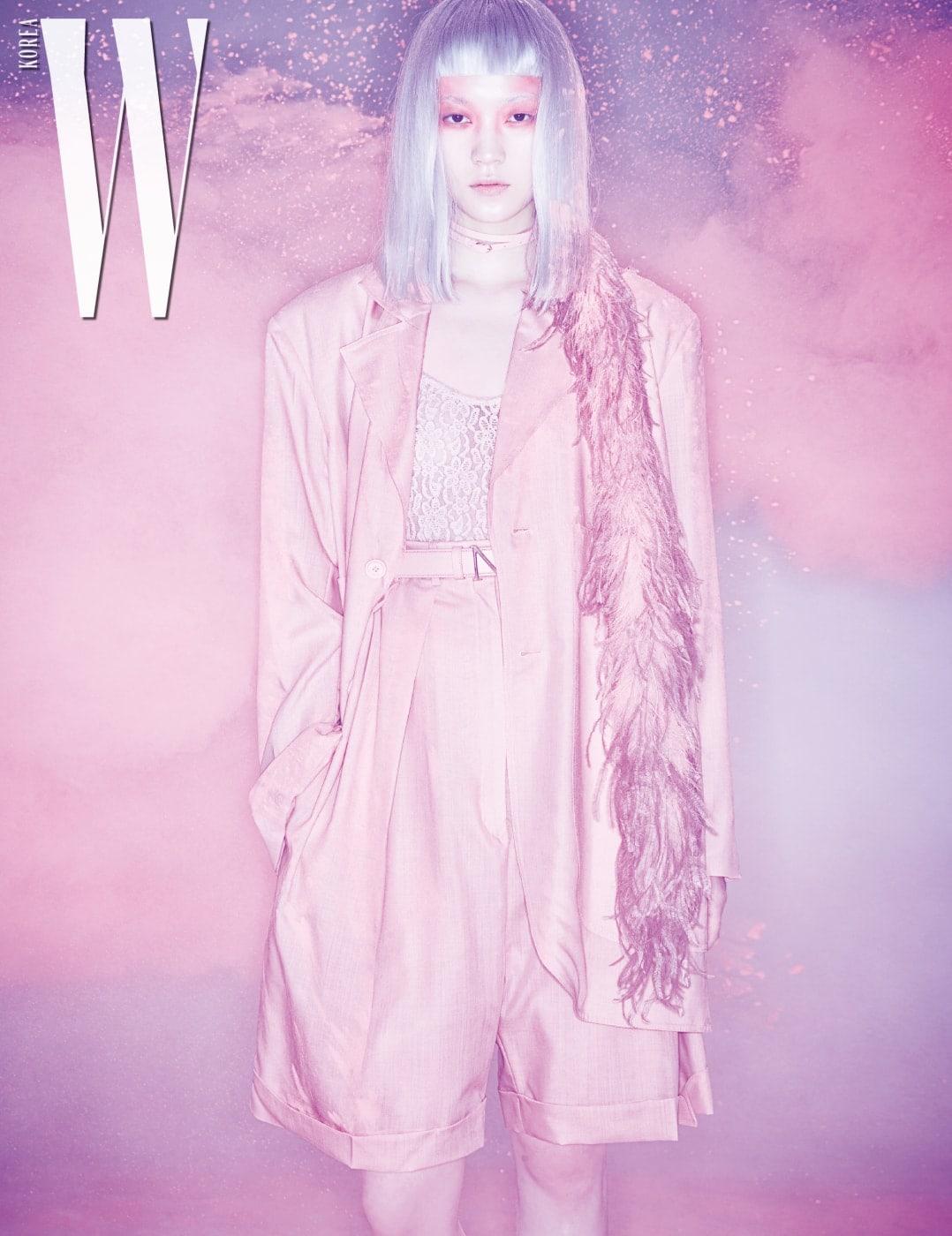 화사한 분홍색 테일러드 재킷과 롤업 팬츠, 레이스 보디슈트, 브랜드의 이니셜을 응용한 금속 버클 벨트, 목걸이로 연출한 섬세한 깃털 장식 벨트는 모두 Nina Ricci 제품.