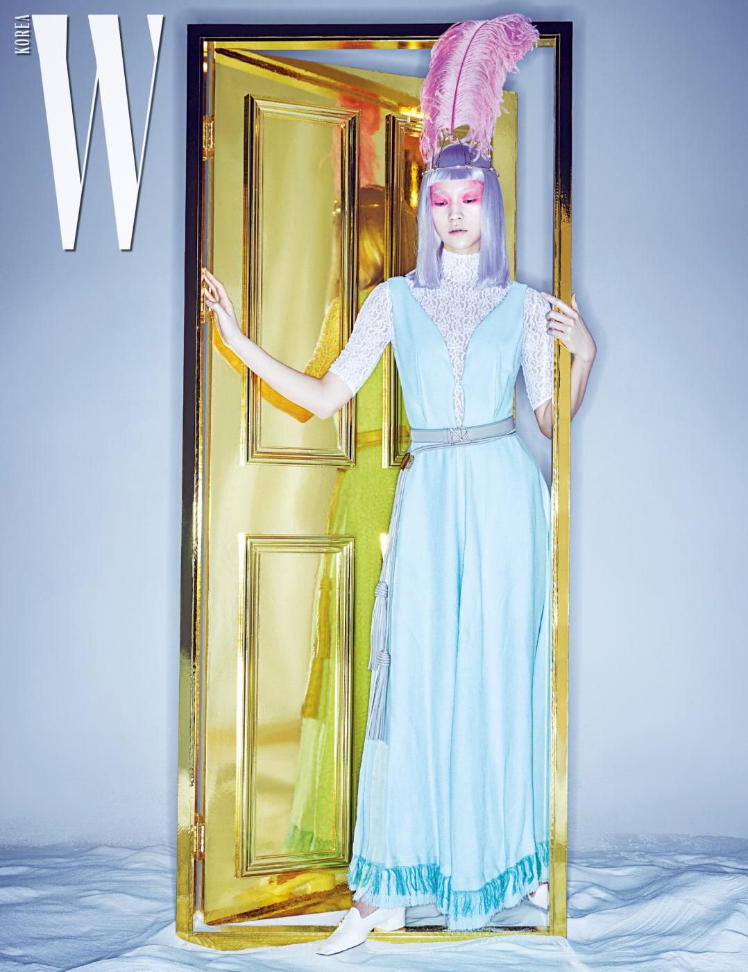 드라마틱한 깃털 헤드피스, 레이스 보디슈트, 유연한 실루엣이 돋보이는 맥시 드레스,  버클 장식 가죽 벨트, 태슬 장식 가죽 벨트,  로퍼는 모두 Nina Ricci 제품.