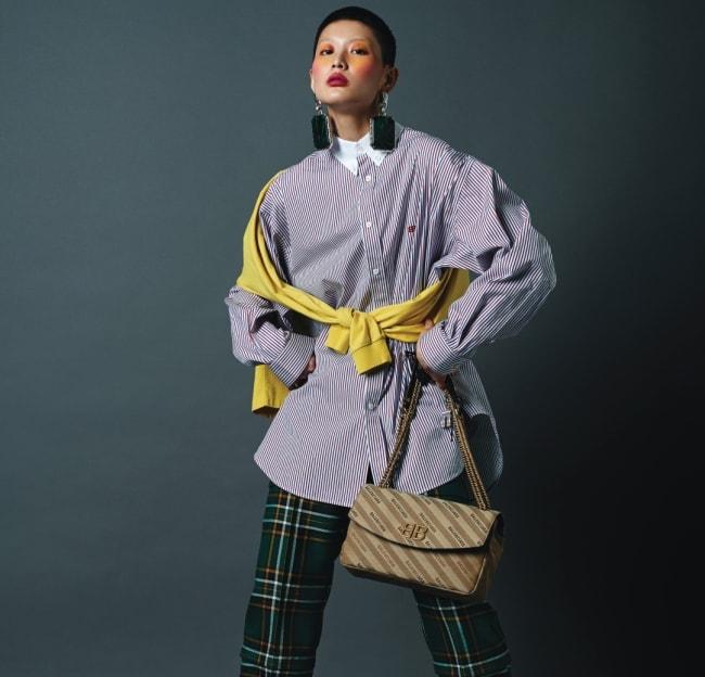 볼드한 원석 귀고리, 스웨트셔츠를 겹친 듯 연출한 줄무늬 셔츠, 집업 장식의 체크 팬츠, BB 로고 장식 백, 스파이크 샌들은 모두 발렌시아가 제품.