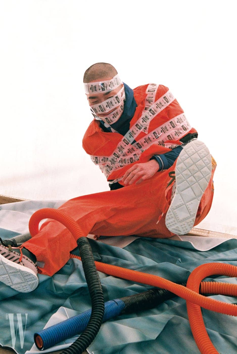 오렌지색 워크 셔츠와 팬츠는 Brahmane, 안에 입은 후드 재킷은 Sandro, 스니커즈는 Valentino 제품.