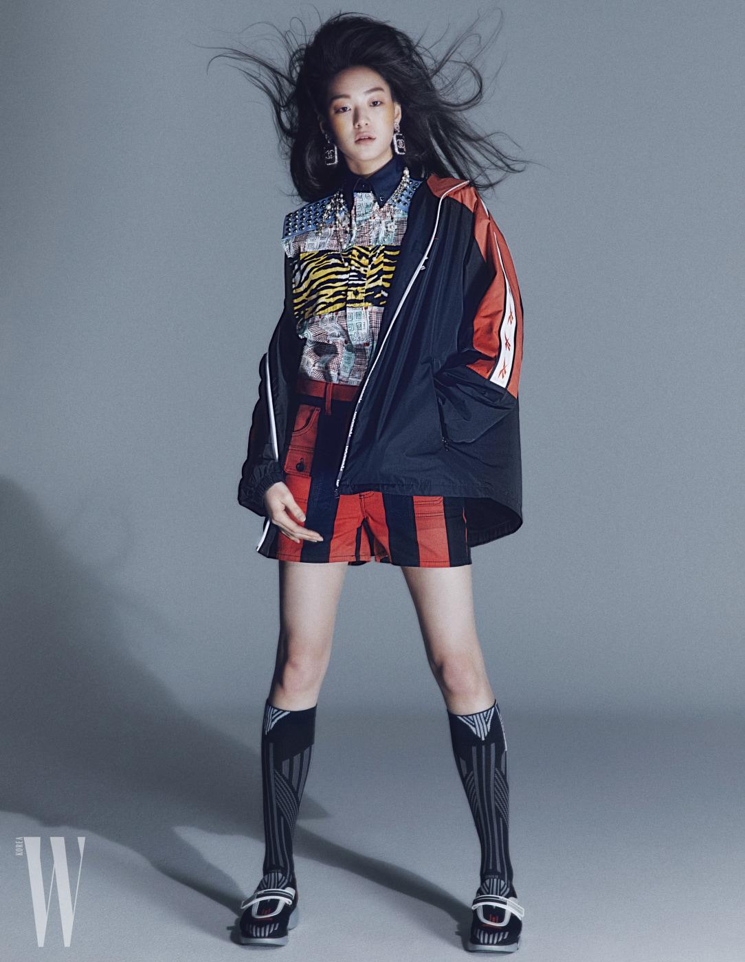 검은색, 빨간색의 집업 재킷은 리복, 화려한 패턴 셔츠, 줄무늬 쇼츠, 클라우드 스니커즈, 삭스는 프라다, 진주 목걸이와 로고 귀고리는 샤넬 제품.