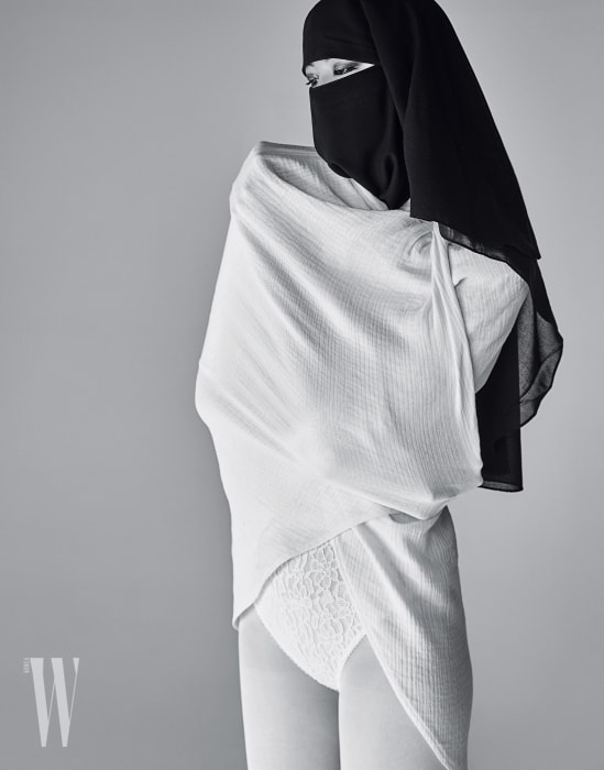하얀색 케이프와 안에 입은 레이스 보디슈트는NinaRicci 제품.