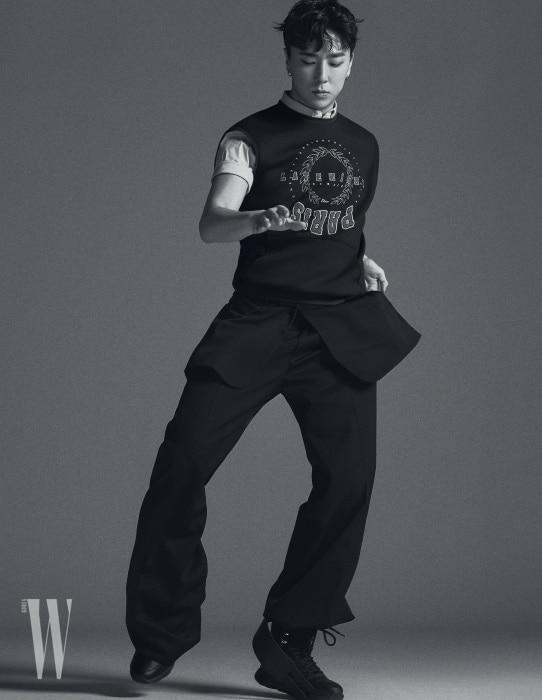 자수 장식 니트 베스트와 반소매 셔츠, 안에 겹쳐 입은 재킷, 통이 넓은 검정 팬츠, 부츠 모양의 스니커즈는 모두 디올 옴므 제품.