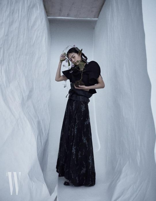 아방가르드한 톱은 Commes des Garcons, 가죽 벨트는 &Otherstories, 잔잔한 꽃이 그려진 롱스커트는 H&M Conscious, 슬라이드는 Burberry 제품.