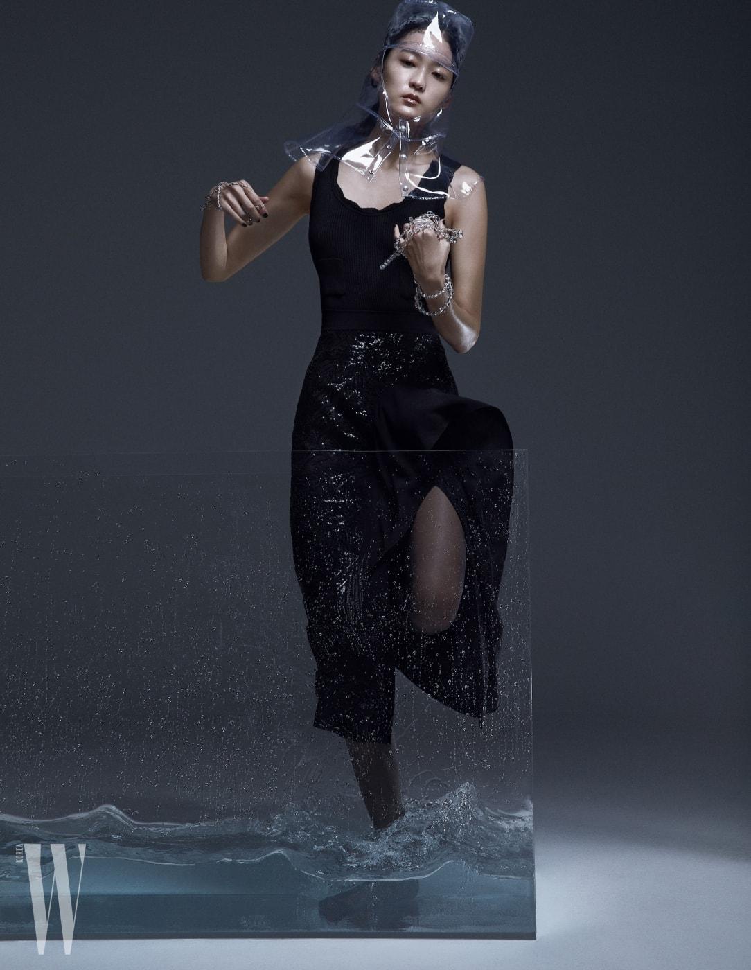 투명한 비닐 모자와 니트 보디슈트, 손에 든 구슬 목걸이는 모두 Chanel, 스팽글 장식 스커트는 Michael Kors 제품.