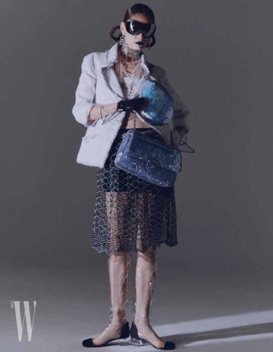 시퀸 소재 플랩 백과 호보 백, 미래적인 고글 선글라스, 트위드 재킷, 크롭트 톱, 쇼츠, 시스루 스커트, 글러브, 귀고리, 목걸이, PVC 소재의 하이 부츠는 모두 Chanel 제품.