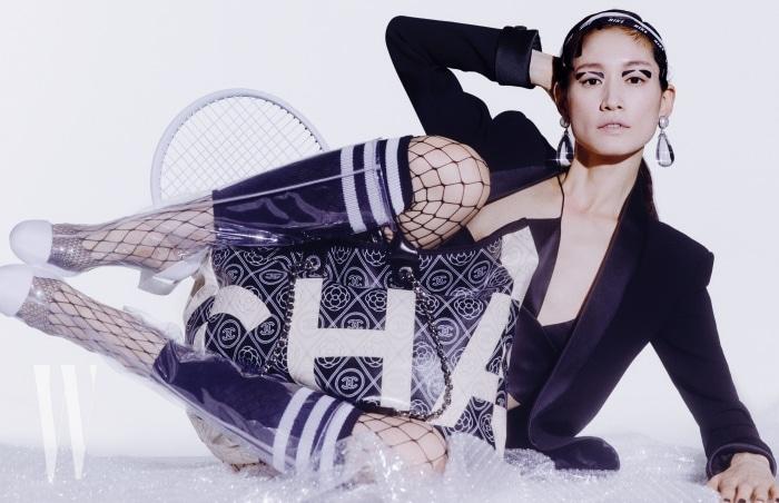 아이코닉한 로고와 까멜리아 패턴이 강조된 큼직한 쇼퍼백, 턱시도 재킷, 물방울 모양의 투명한 귀고리, PVC 소재의 하이 부츠는 모두 Chanel 제품. 브라톱, 헤드밴드, 타이츠, 레그웨어는 모두 스타일리스트 소장품.