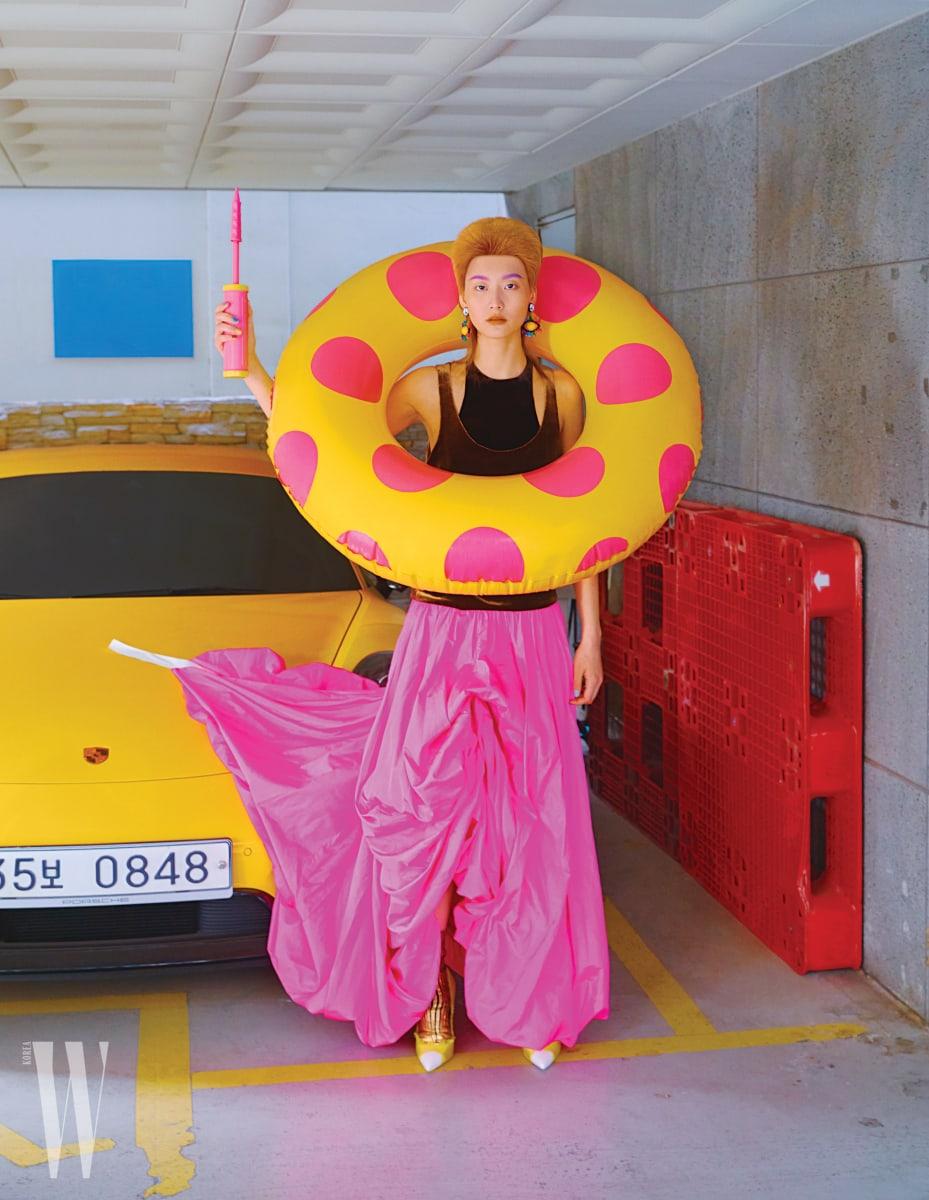 푸크시아 핑크 색상의 스커트가 돋보이는 드레스는 Valentino, 귀고리는 Bimba Y Lola, 슈즈는 Tom Ford 제품.