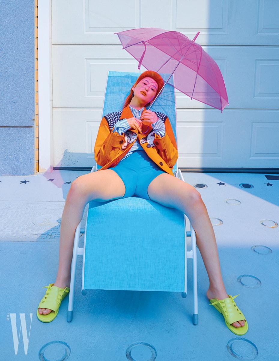 줄무늬 셔츠와 스터드 장식의 주홍색 가죽 재킷은 Prada, 팬츠는 La Perla, 레몬색 러버 소재 플랫 슈즈는 Melissa by Mdreams 제품.