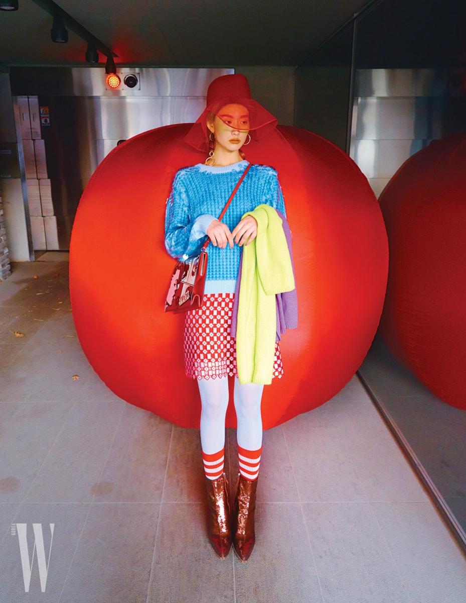모자는 YCH, 파란색 시퀸 장식 스웨터는 Marc Jacobs, 기하학적인 패턴의 붉은색 스커트는 Sandro, 귀고리는 H&M, 카툰 프린트의 크로스백은 Prada, 팔에 건 니트 머플러는 둘 다 Hermes, 줄무늬 양말은 Oui Paname, 시퀸 장식 슈즈는 Emilio Pucci 제품.