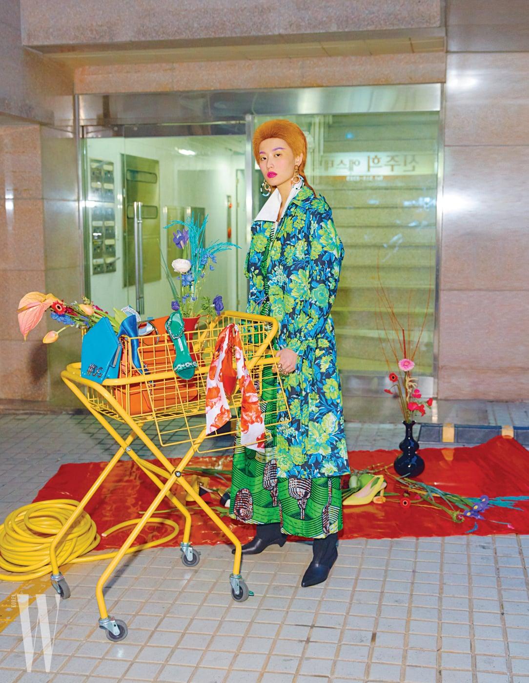 꽃무늬 트렌치코트는 MSGM by ihanstyle.com, 흰색 칼라가 돋보이는 화려한 프린트의 롱 드레스와 검정 부츠는Stella McCartney, 조형적인 귀고리는 Bimba Y Lola, 반지는 Bottega Veneta 제품. 카트에 놓인 오각형의 하늘색 페이턴트 가죽 백은 Dolce & Gabbana, 파란색, 초록색, 하늘색의 주얼 장식 새틴 힐은 모두 Manolo Blahnik, 큼직한 붉은색 가죽 백과 스카프 장식의 붉은색 페이턴트 힐은 Salvatore Ferragamo 제품. 바닥에 놓인 컬러 블록 패턴의 로퍼는 Bally, 검정 스톤 장식의 노란색 로퍼와 레몬색 슬링백 슈즈는 Stuart Weitzman 제품.