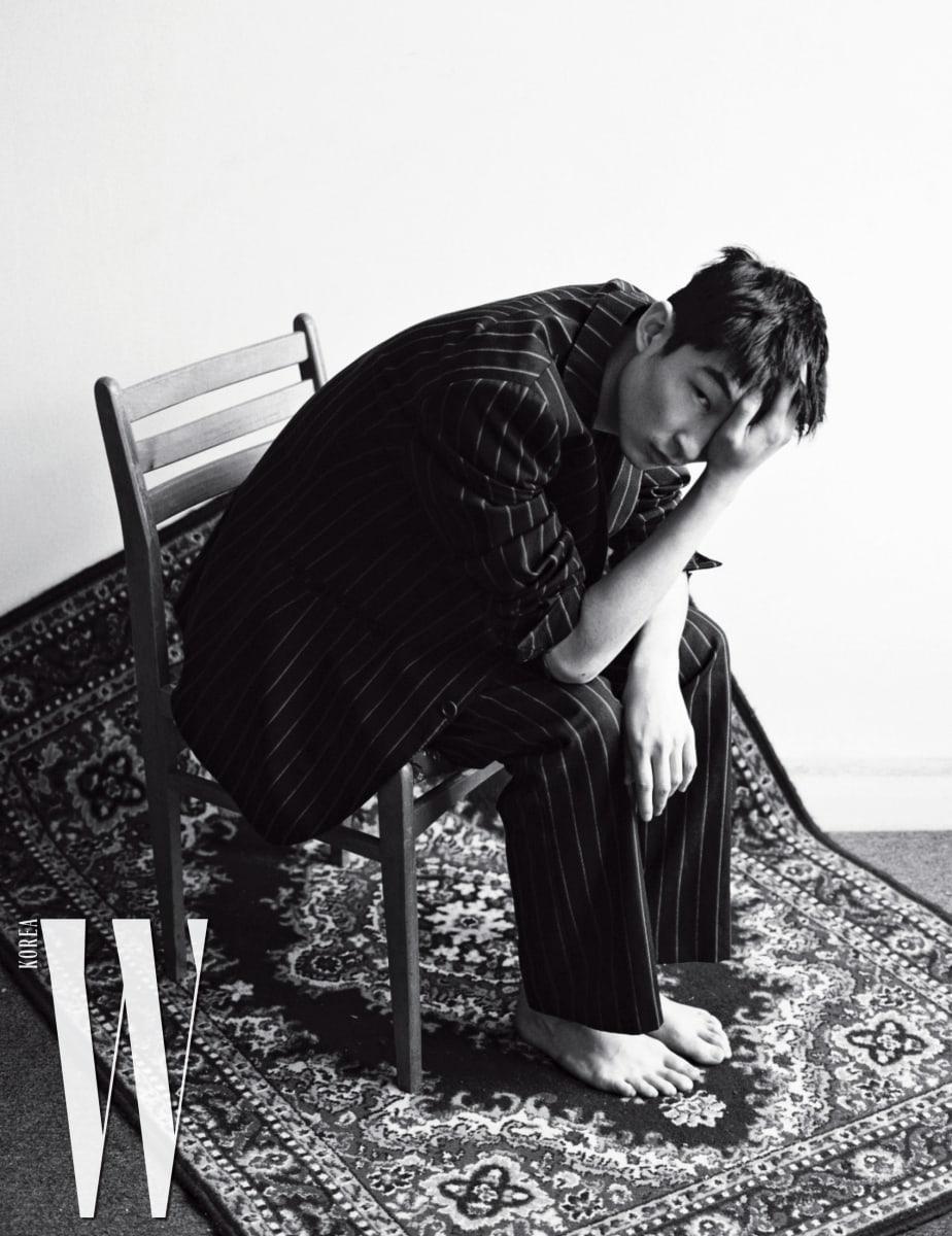 주목받는 아티스트이자 세계적으로 유명한 모델이기도 한 김상우는 예술계와 패션계를 넘나들며 활약하고 있다. 줄무늬 슈트는 본인의 것.