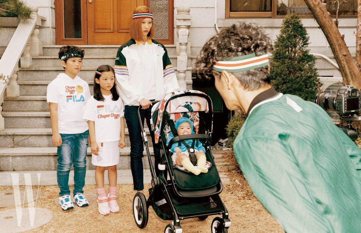 오빠가 착용한 츕파춥스 프린트 티셔츠는 Fila Kids, 줄무늬 헤드밴드는 Flakkiki, 운동화는 Prospecs Kids 제품 . 언니가 착용한 티셔츠와 스커트는 Fila Kids, 운동화는 Prospecs Kids 제품. 엄마가 착용한 아노락 점퍼는 Lacoste Collection, 피케 셔츠와 데님 진은 Lacoste, 줄무늬 헤드밴드는 The Studio K 제품 . 유모차는 Bugaboo 제품. 아빠가 착용한 초록색 점퍼는 Alexander Wang, 헤드밴드는 The Studio K 제품 .
