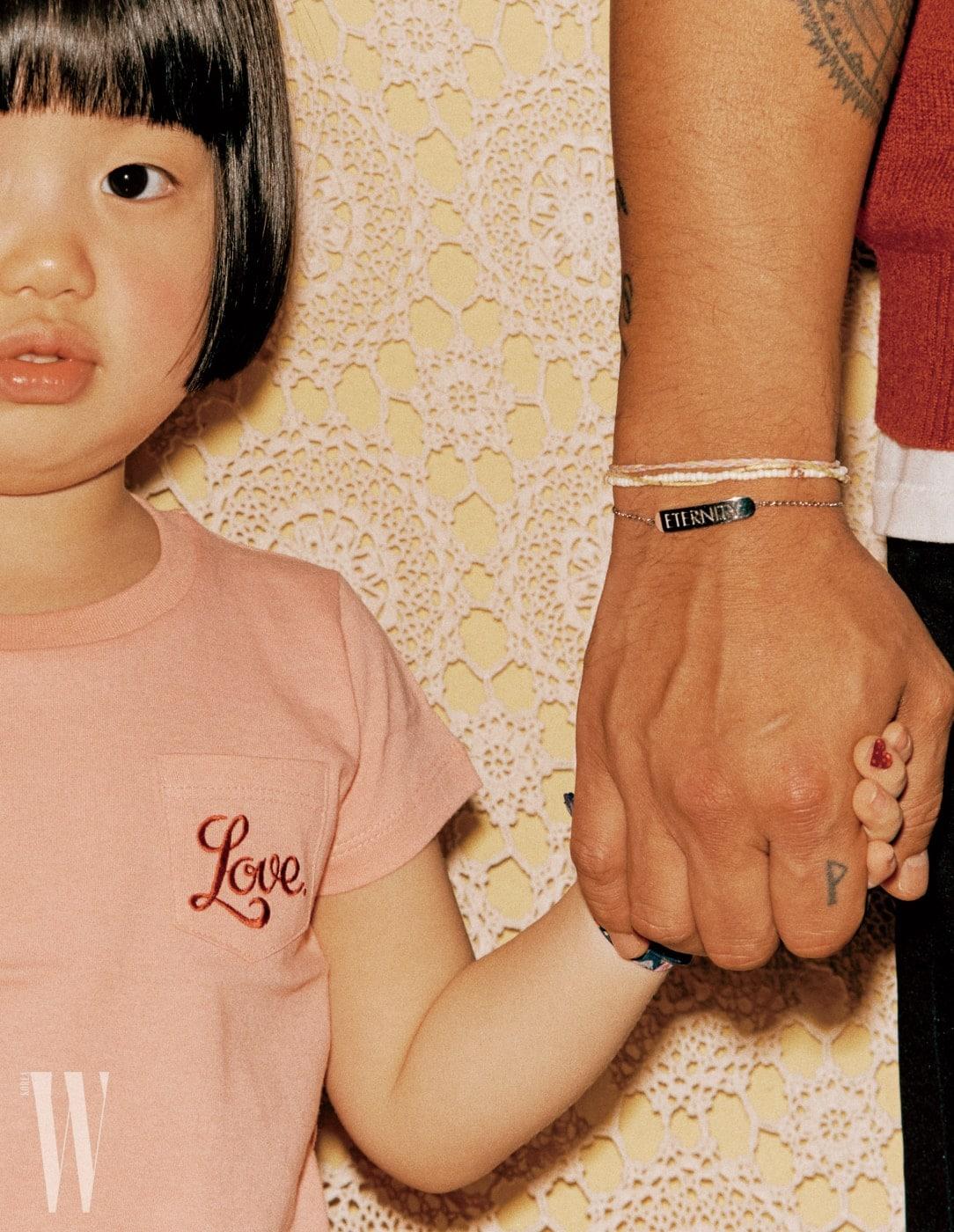 아이가 착용한 분홍색 러브 티셔츠는 Love., 패브릭 팔찌는 H&M Kids 제품. 아빠가 착용한 팔찌는 Calvin Klein Watches + Jewelry 제품.