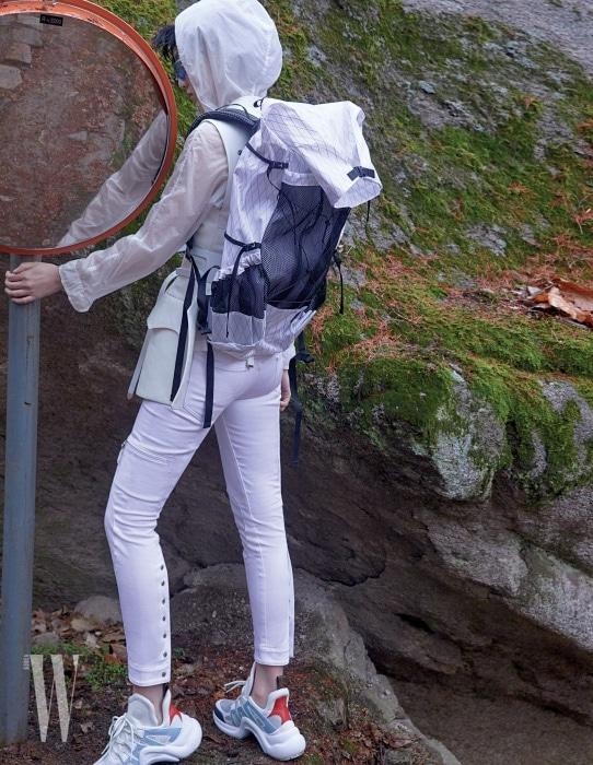 버클 베스트와 팬츠, 와이드 벨트, 아치라이트 스니커즈는 루이 비통, 흰색 아노락 재킷은 맥케이지, 메시 포켓 백팩은 케일 by 펄스101, 스포츠 선글라스는 난니니 by 시티핸즈컴퍼니 제품.