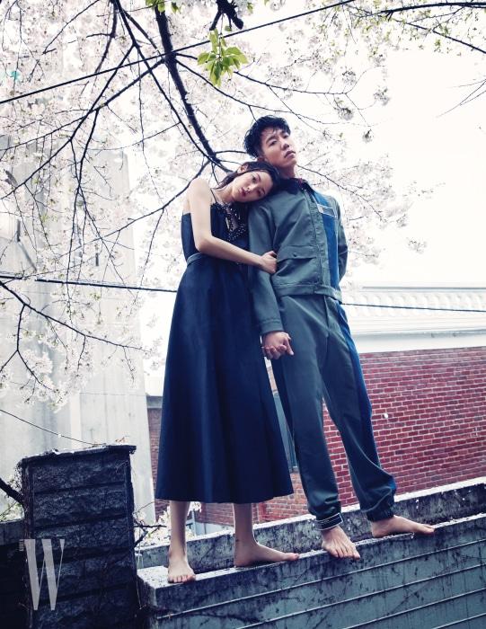 티아나가 입은 가슴 부분에 비주가 장식된 검은색 드레스는 Miu Miu 제품 . 다니엘이 입은 블루종과 스트랩 팬츠는 Prada 제품 .