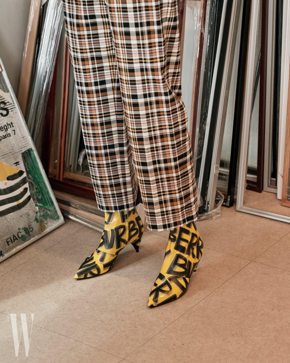 체크무늬 팬츠, 그라피티 프린트 앵클부츠는 버버리 제품.
