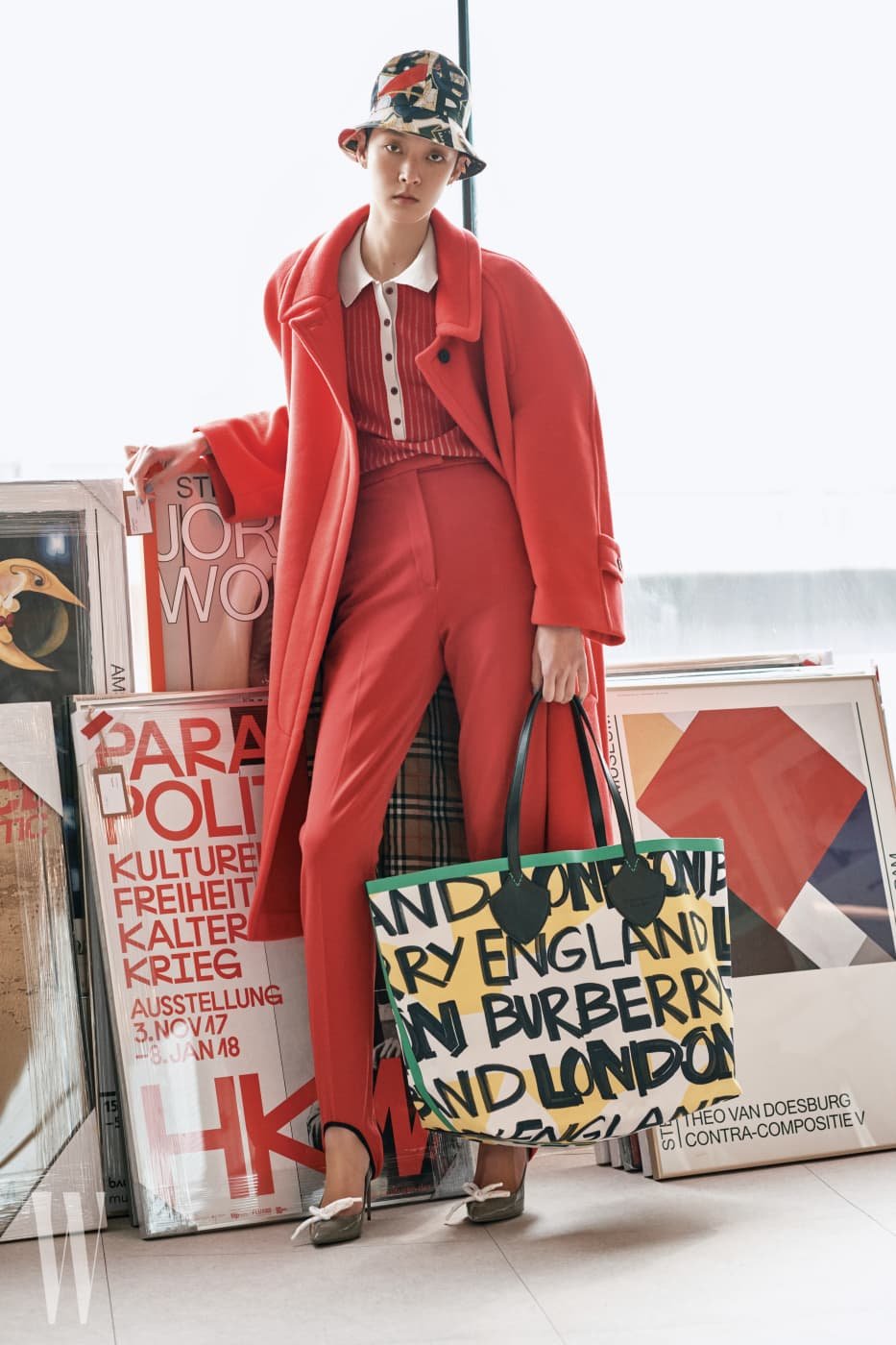 빨간색 립 니트 폴로 셔츠, 빨강 카 코트, 하이웨이스트 승마바지, 로프 장식 회색 스틸레토 힐 슈즈, 멀티 컬러 그라피티 프린트 버킷 모자, 그라피티 프린트 자이언트 토트백은 모두 버버리 제품.