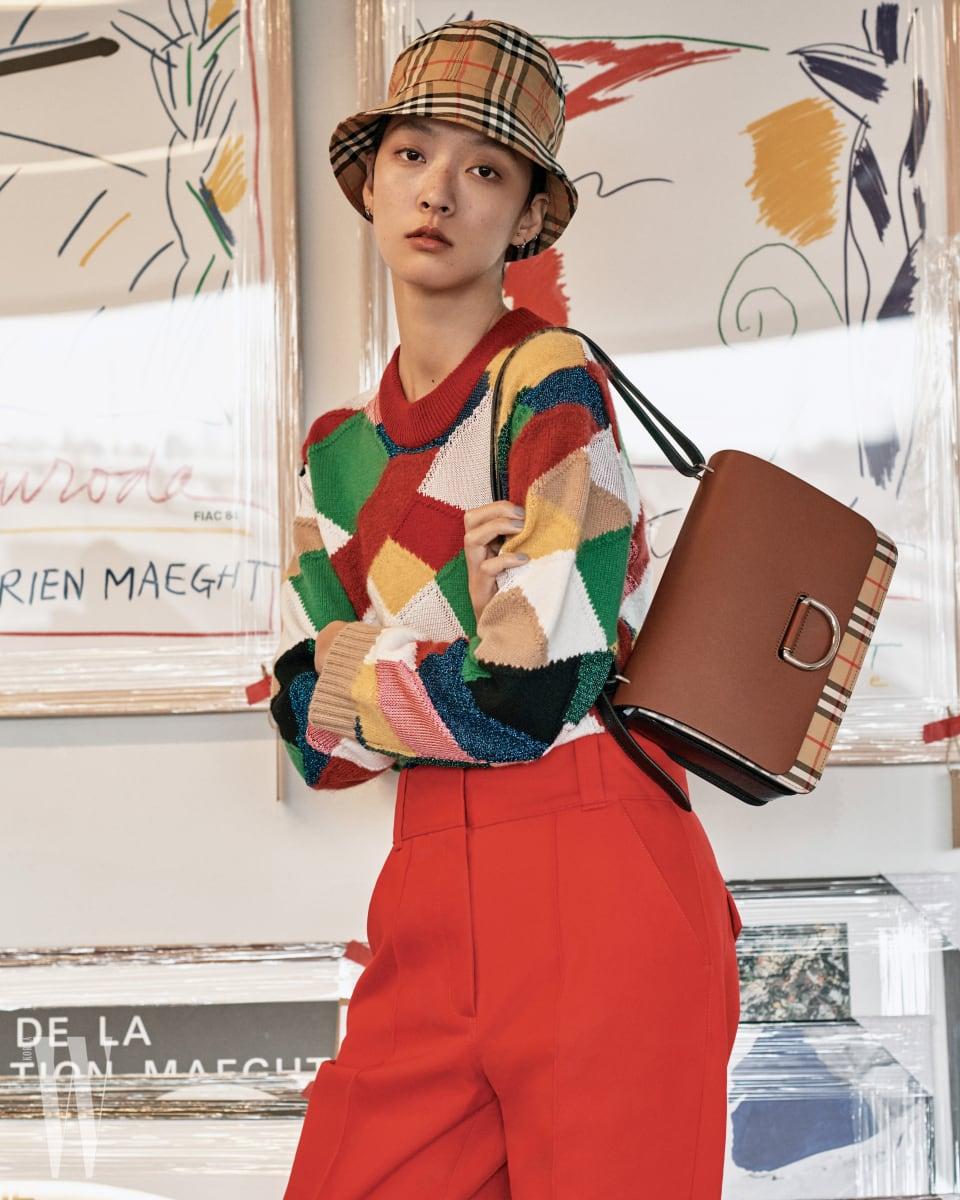 서로 다른 소재의 천 조각이 패치워크된 니트와 빨강 팬츠, 빈티지 체크 버킷 모자, 빈티지 체크 코튼과 가죽이 조합된 D-링 백은 모두 버버리 제품.