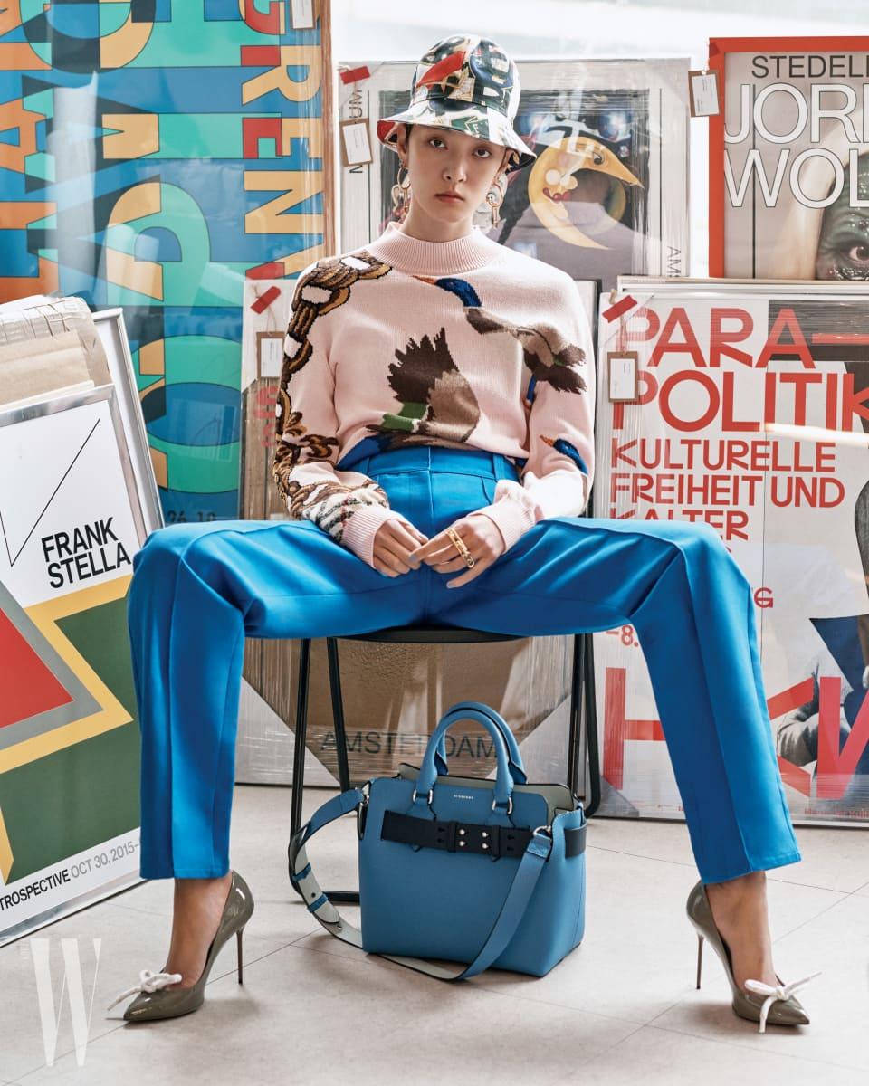 연한 핑크색 오리 무늬 스웨터, 파란색 팬츠, 로프 장식의 회색 스틸레토 힐 슈즈, 멀티 컬러 그라피티 프린트 버킷 모자, 바닥에 놓인 하이드렌지 블루 컬러 스몰 벨트 백, 큼직한 이어링과 링은 모두 버버리 제품.