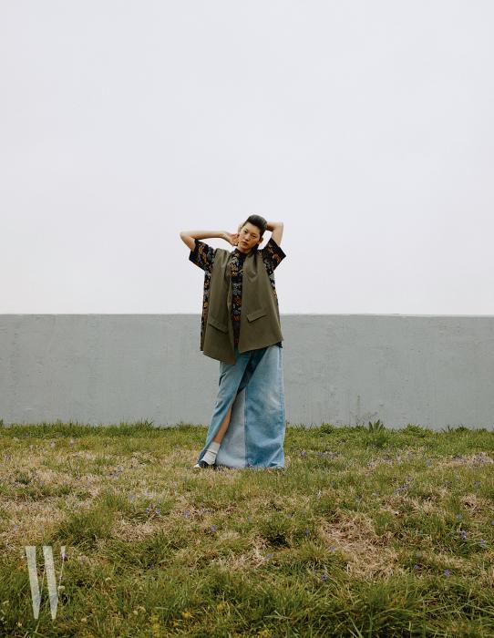 꽃무늬 폴로 셔츠, 재킷을 해체한 베스트는 셀린, 레이스업 슈즈는 트리커즈 바이 유니페어, 트위스트 데님 팬츠는 발렌시아가 제품.