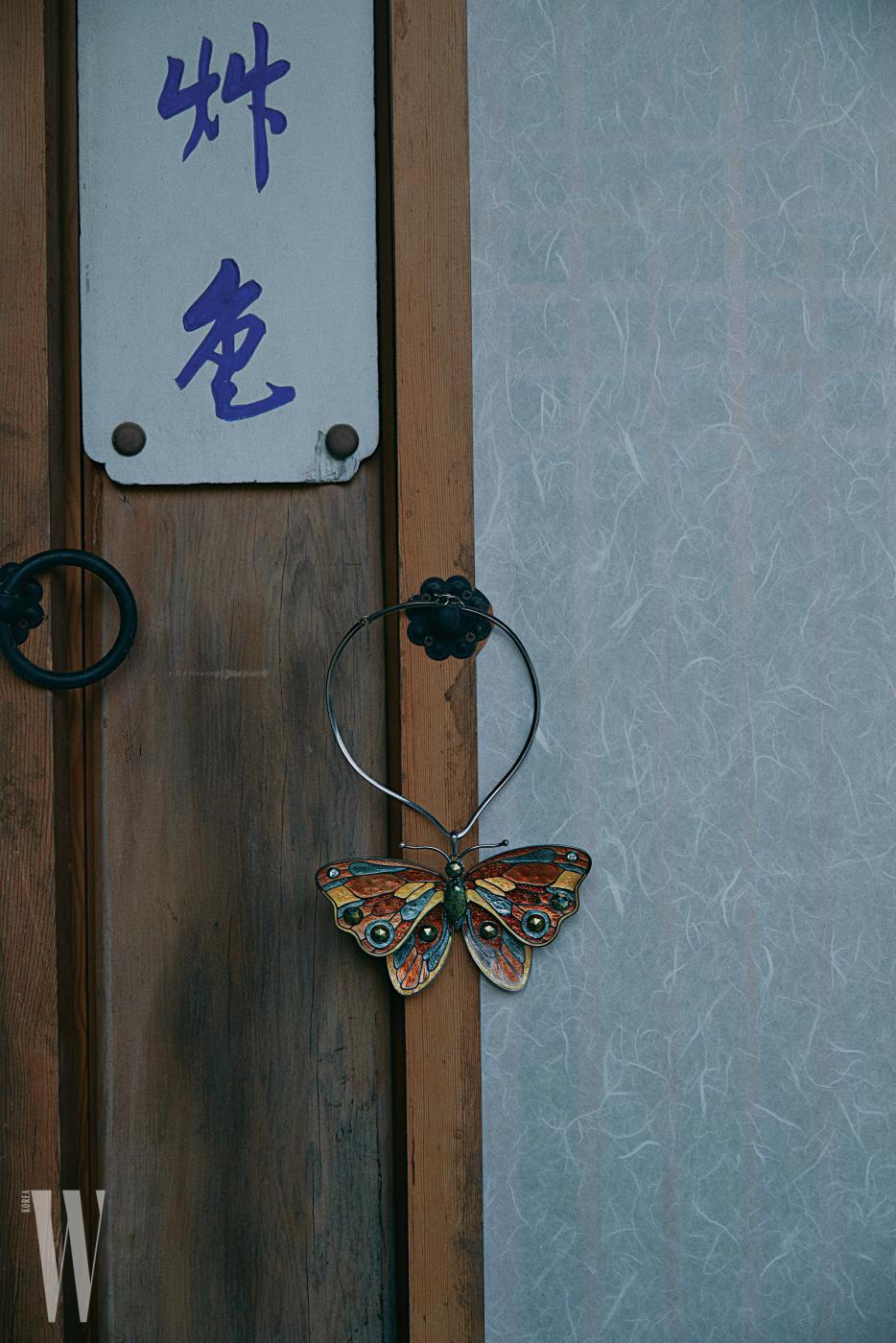 자개 조각을 맞춰 완성한 나비 목걸이는 보테가 베네타 제품.