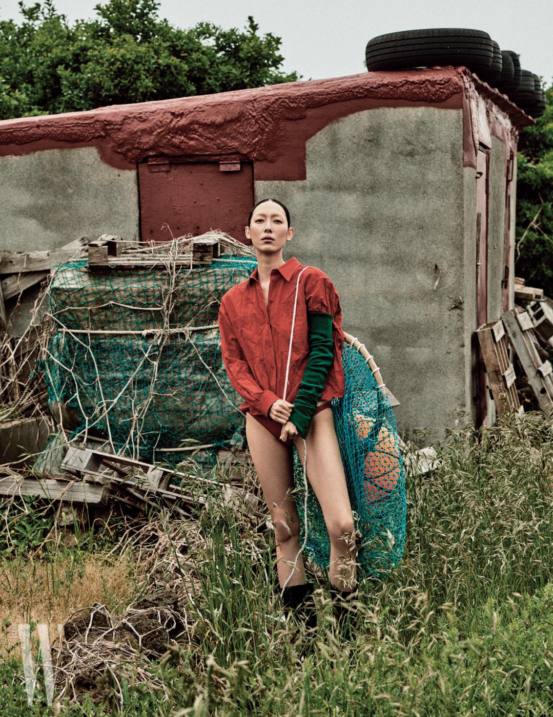 자연스러운 구김이 멋진 셔츠는 Ports 1961, 초록색 팔 워머는 Rick Owens, 빨간색 수영복은 Hermes, 검은색 부츠는 Calvin Klein Jeans 제품.