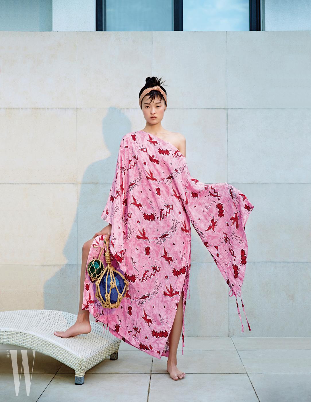 그래픽적인 새가 그려진 화려한 원숄더 드레스는 파울라 이비자 컬렉션으로, 로에베 제품. 헤어 밴드는 헬렌 카민스키 제품.