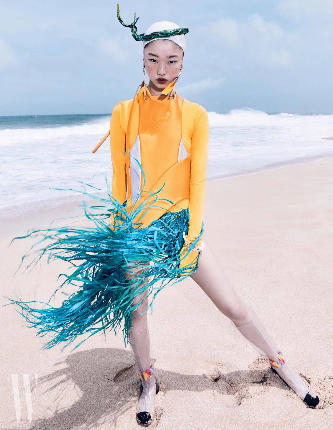 노란색보디슈트, 서핑슈트디자인을차용한베스트는Kijun, 부츠는Chanel, 귀고리는Free People 제품.