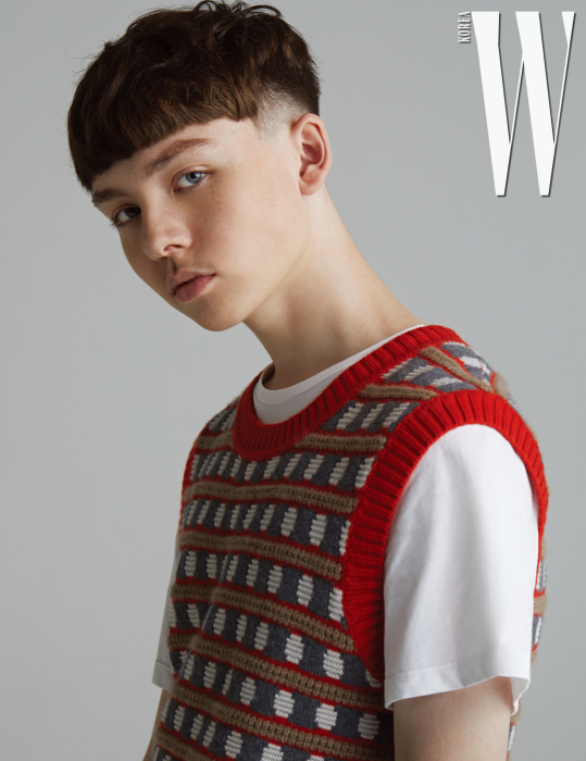 마틴이 입은 화려한 무늬의 슬리브리스 니트는 버버리, 안에 입은 화이트 티셔츠는 캘빈클라인 진 제품.