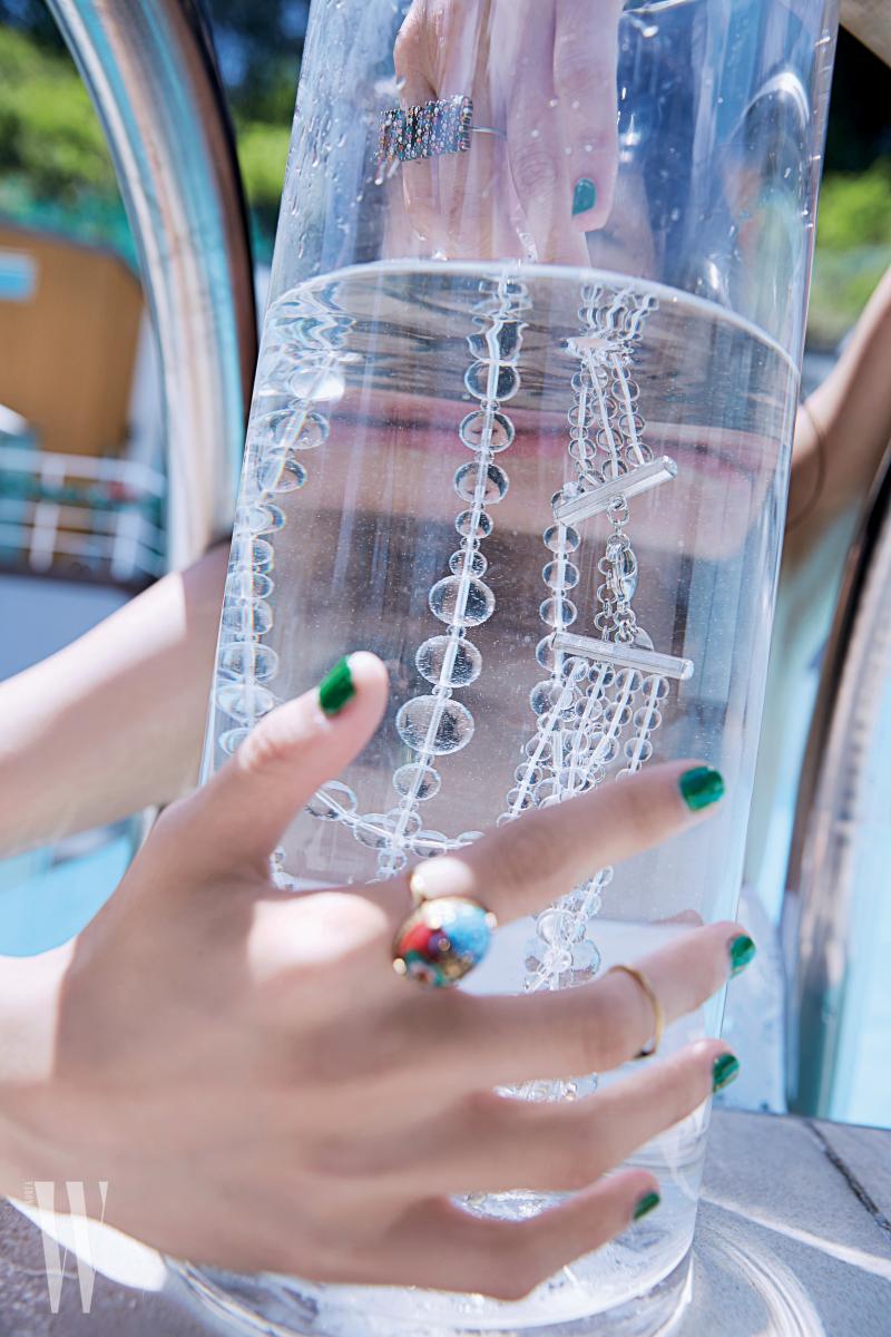 크고 작은 동그란 형태의 투명한 구슬 목걸이는 샤넬 제품. 가격 미정. 컬러풀한 반지는 디올 제품. 40만원대.