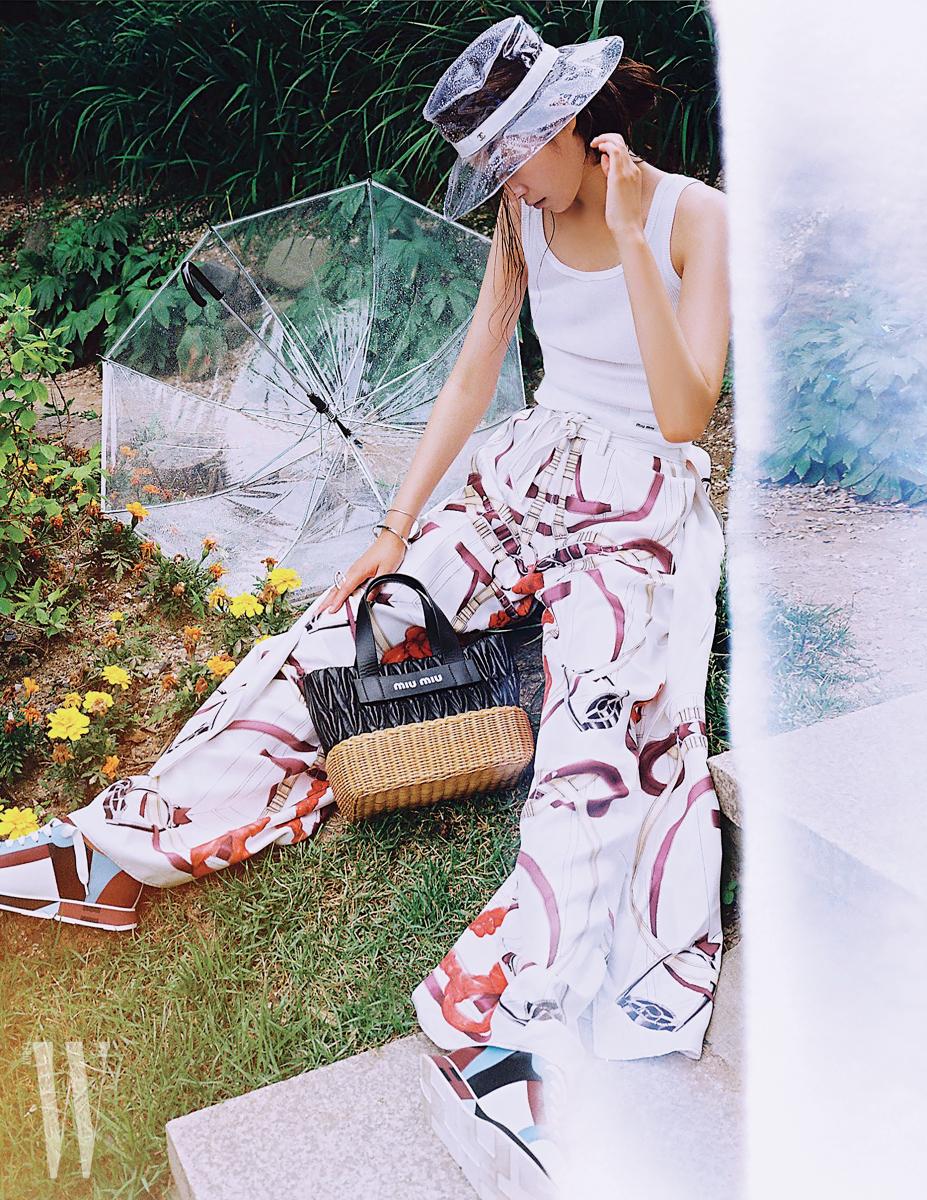 슬리브리스 톱과 라탄 소재가 어우러진 백은 미우미우, 실크 팬츠와 스니커즈는 에르메스, PVC 소재 투명 모자는 샤넬, 링과 브레이슬릿은 코스 제품.