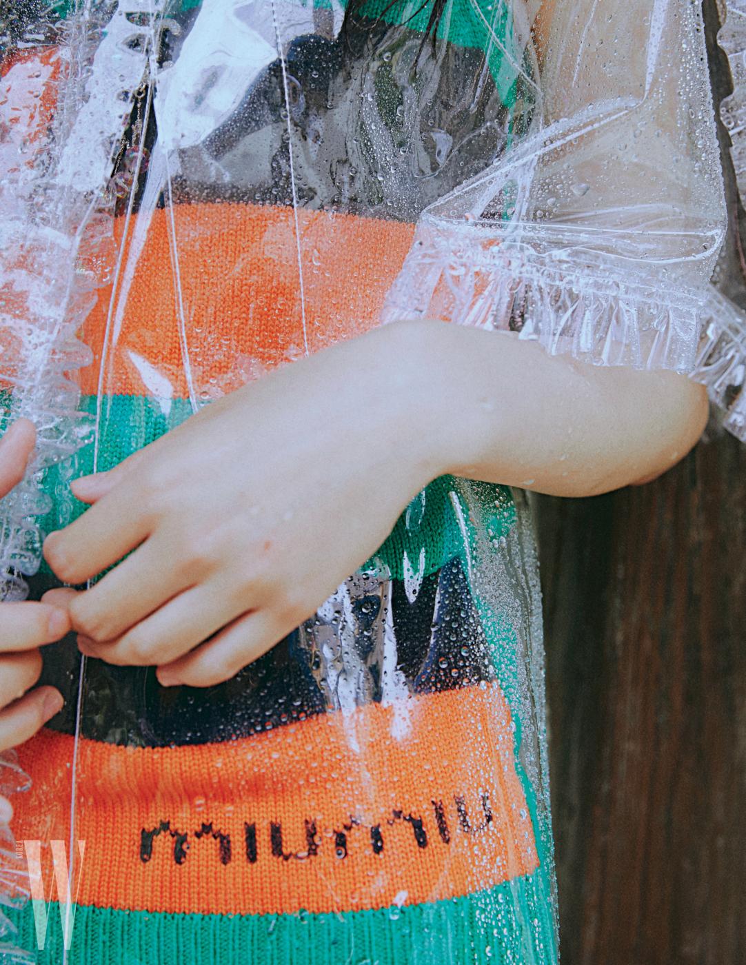 러플 장식의 투명 PVC 케이프는 샤넬, 니트 소재의 배색 슬리브리스는 미우미우 제품.
