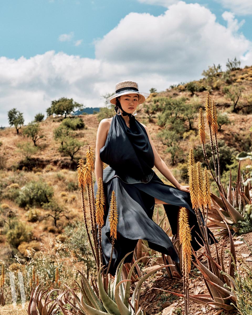 구조적인 실루엣의 드레스는 Celine, 투명한 이어링과 PVC 소재 모자는 Chanel, 라피아 소재 모자는 Evance 제품.