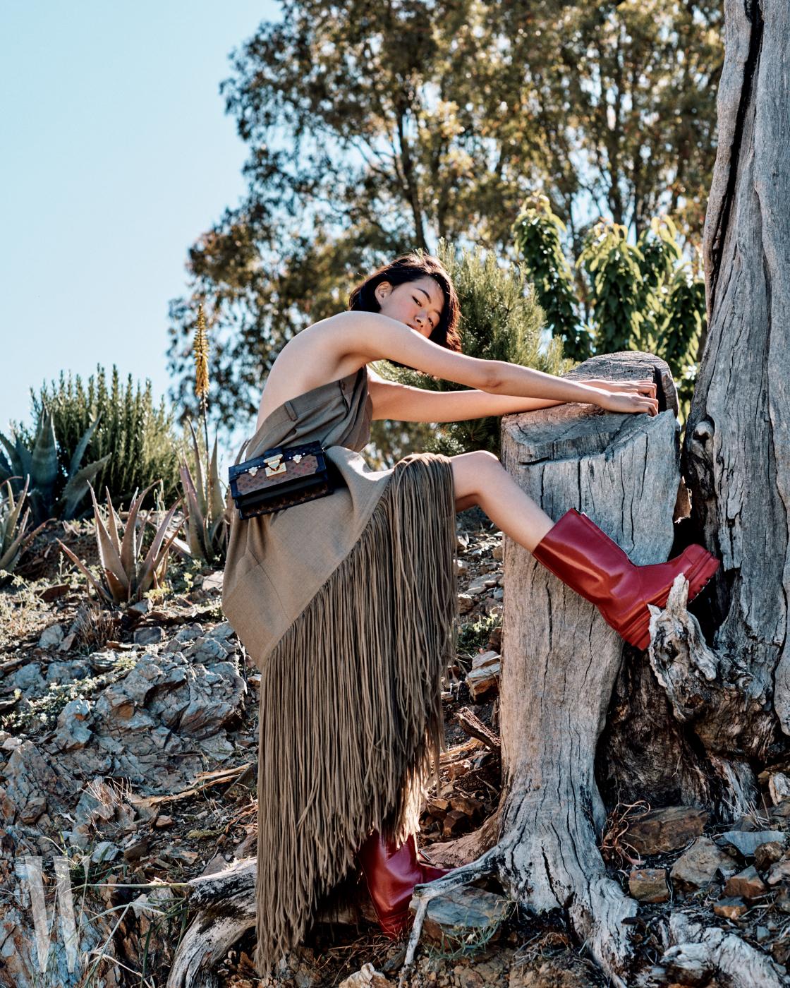 프린지 드레스는 Celine, 허리에 찬 트렁크 클러치는 Louis Vuitton, 투박한 부츠는 Marni 제품.