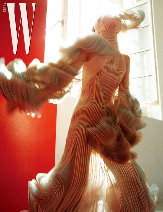 물결같은 곡선적인 실루엣의 시스루 드레스, 헤드피스는 Iris Van Harpen 제품.