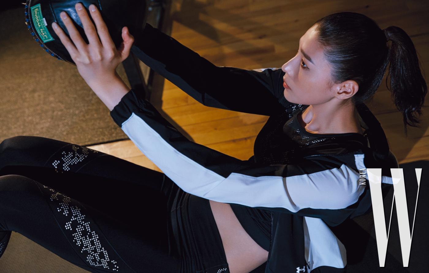 방수 기능과 통기성을 제공하고 뒤트임으로 활동성이 뛰어난 재킷과 뒷면에 반지퍼가 있는 크롭트 톱, 패턴 프린트의 레깅스는 모두 Under Armour 제품.