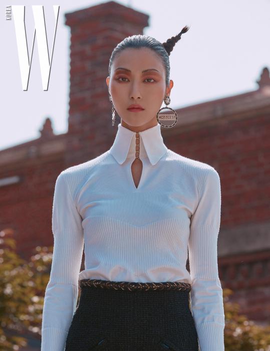 니트 톱, 트위드 스커트, 로고와 진주 장식 링 귀고리는 모두 Chanel 제품.