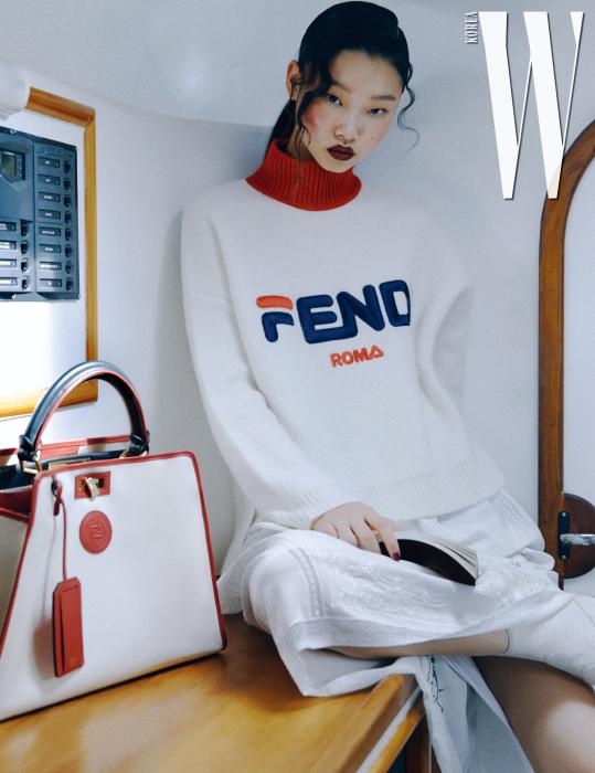 스포티한 터치를 더한 터틀넥 스웨터, 순백의 아일릿 장식 롱스커트, 붉은색 트리밍이 시선을 끄는 패브릭으로 감싼 피카부 백은 모두 Fendi 제품.