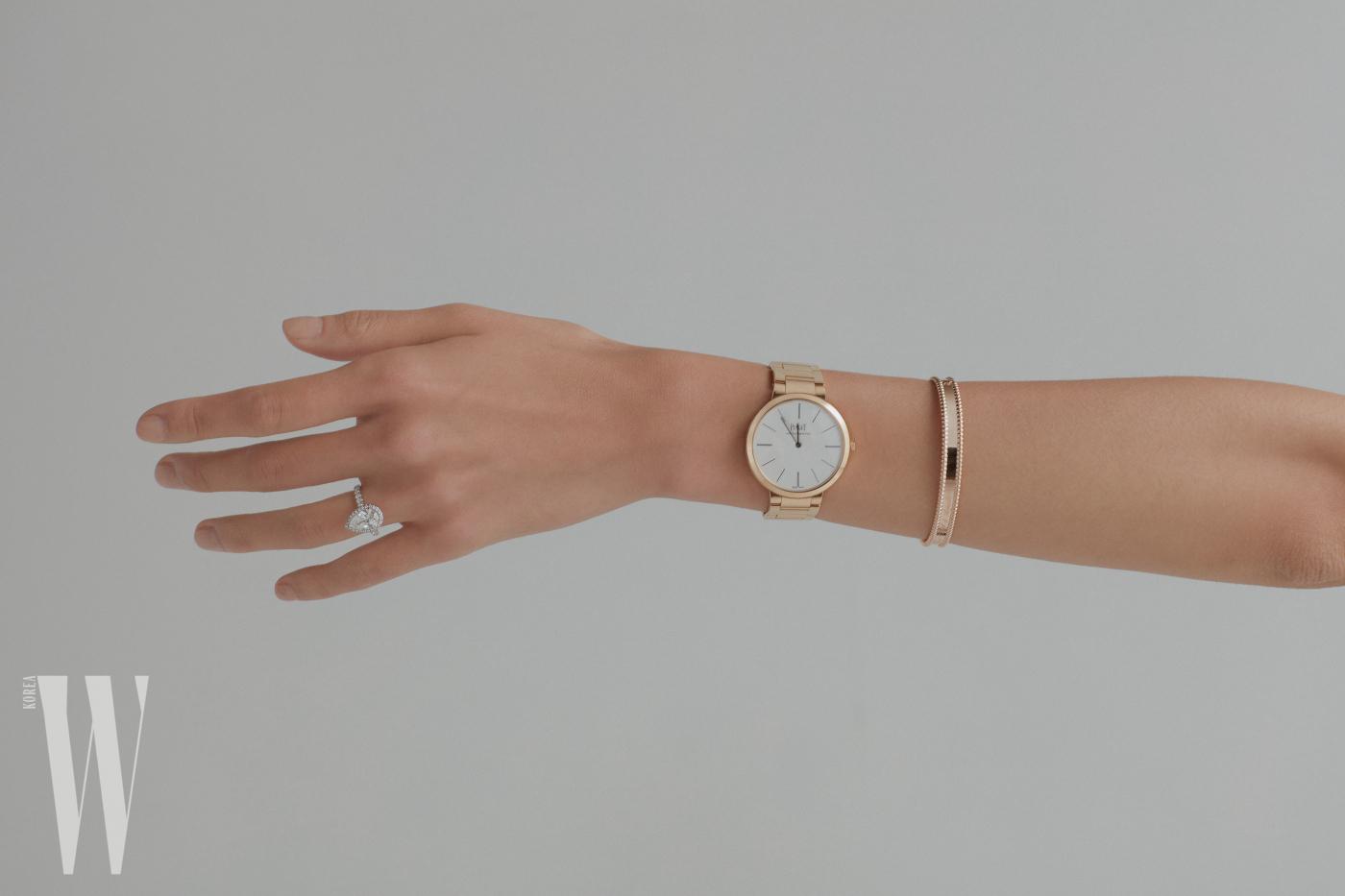 38mm의 큼직한 다이얼과 간결한 디자인이 돋보이는 핑크 골드 알티플라노 시계는 Piaget 제품. 핑크 골드 소재의 빼를리 시그너처 브레이슬릿은 Van Cleef & Arpels 제품. 센터에 2.06캐럿의 페어형 다이아몬드가 볼록하게 솟아 있고, 그 주위를 브릴리언트 컷 다이아몬드가 감싼 매혹적인 자태의 데스티네 솔리테어 링은 Cartier 제품.