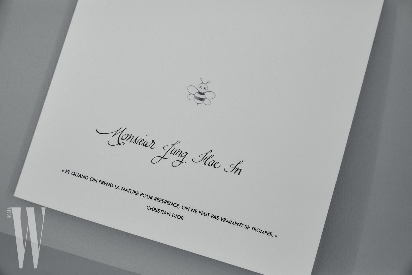 디올의 상징적인 꿀벌 심벌에 카우스 특유의 X 마크를 위트 있게 더한 초대장.