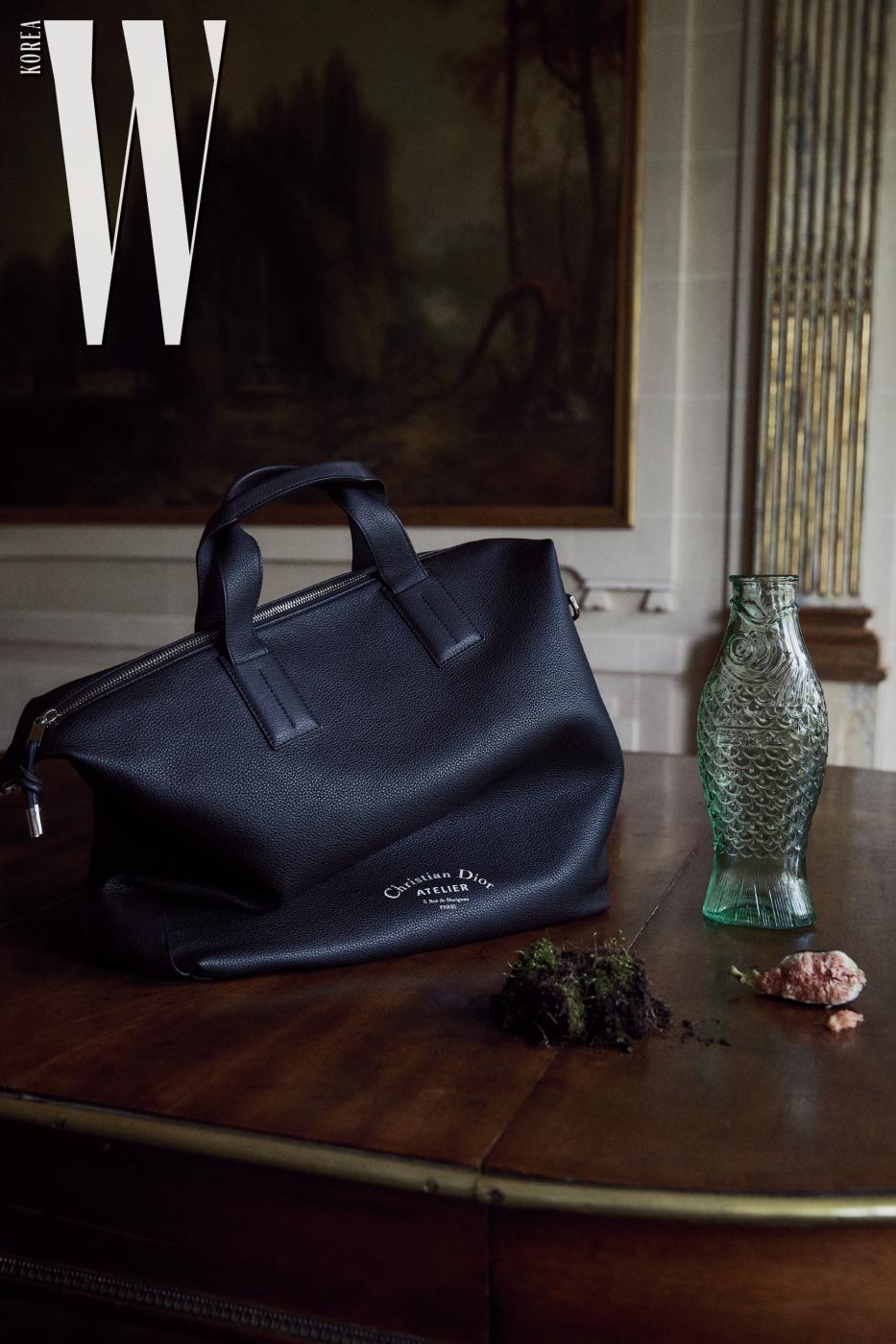 크리스찬 디올 아틀리에 로고 장식을 모던하게  더한 가죽 토트백은 Dior Men 제품.