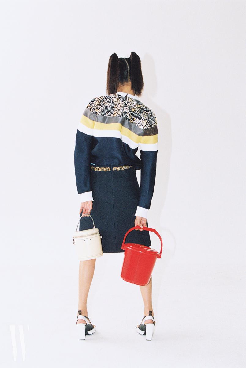 네오프렌 소재의 톱과 스커트, 하얀색 슈즈는 루이 비통 제품. 가격 미정. 왼손에 든 하얀 원통 가방의 사이즈는 15cm×16.5cm, 무게는 580g. 루이 비통 제품. 2백88만원.