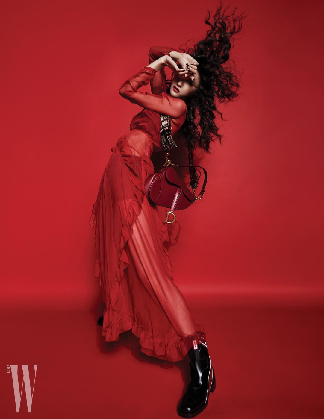 붉은색 시스루 드레스, 이너 톱과 브리프, 프린지 장식 핸들이 돋보이는 새들백, 부츠는 모두 Dior 제품.