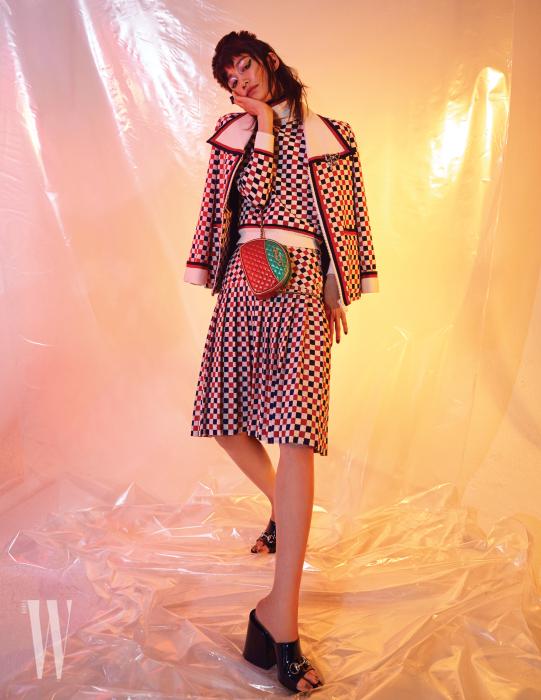 기하학적인 패턴의 재킷과 톱, 스커트, 퀼팅 장식의 메탈릭 가죽 숄더백, 보 형태의 브로치, 반지, 홀스빗 장식 페이턴트 뮬은 모두 Gucci 제품.