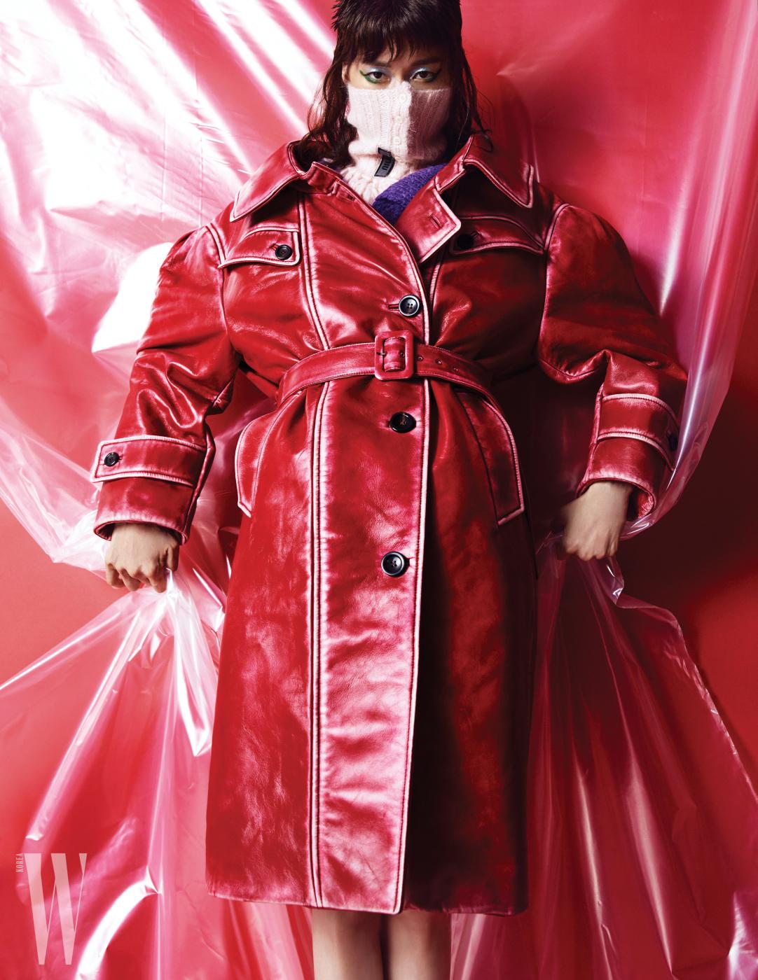 레트로 터치를 더한 강렬한 붉은색의 가죽 트렌치코트, 니트 소재의 로고 장식 넥워머와 톱은 모두 Miu Miu 제품.