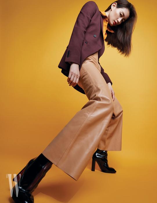 테일러드 재킷, 머스터드 색상이 감미로운 셔츠, 유연한 실루엣의 가죽 와이드 팬츠는 모두 Salvatore Ferragamo 제품. 앵클부츠는 Alexander McQueen 제품.