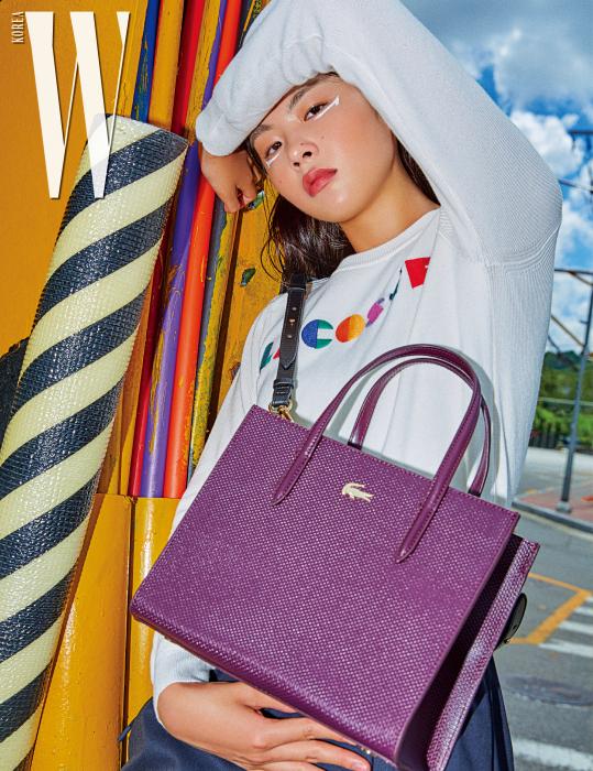 형형색색의 로고가 돋보이는 니트 톱과 네이비 색상 스커트, 보라색 샨타코 백은 모두 Lacoste 제품.