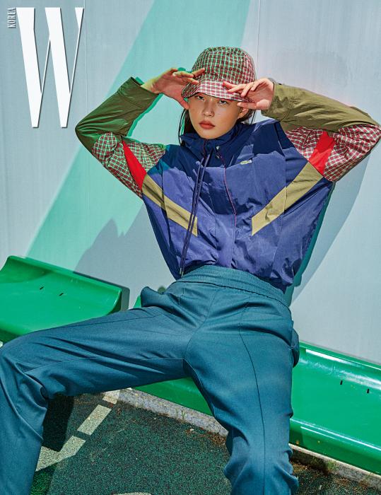 네이비와 카키 체크 패턴이 믹스된 트랙 재킷과 녹색 트레이닝팬츠, 체크 버킷햇은 모두 Lacoste 제품.