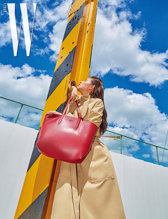 트렌치코트와 버건디 색상의 안나 백은 Lacoste 제품